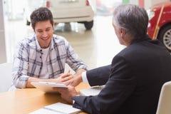 Verkäufer, kunden zeigend, wo man das Abkommen unterzeichnet Lizenzfreie Stockbilder