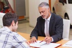 Verkäufer, kunden zeigend, wo man das Abkommen unterzeichnet Stockbilder