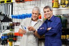 Verkäufer mit Kunden-Holding verpacktem Werkzeug Stockfotografie