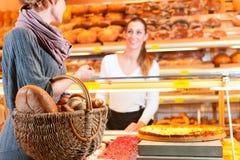 Verkäufer mit weiblichem Abnehmer in der Bäckerei Stockbilder
