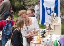 Verkäufer - Teilnehmer des Festivals zeigt einem Besucher ein handgemachtes Spielzeug am Purim-Festival mit König Arthur in der S lizenzfreies stockbild