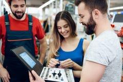 Verkäufer zeigt Paare des neuen Werkzeugkastens der Kunden im Elektrowerkzeugspeicher lizenzfreies stockbild