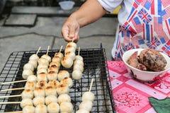 Verkäufergrillschweinefleisch-Fleischklöschentoast auf dem Grill Stockbilder