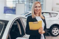 Verkäuferin, die am Auto-Vertragshändler arbeitet lizenzfreie stockbilder