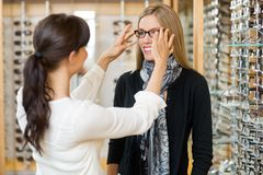 Verkäuferin, die Kunden zu in tragenden Gläsern unterstützt Stockfotos