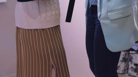 Verk?ufer hilft Dame in der beige Strickjacke sich setzte an und Lederg?rtel zu entfernen in SpeicherUmkleidekabinezeitlupe stock video footage