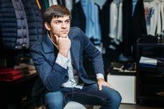 Verkauf, Einkaufen, Mode, Art und Leutekonzept - eleganter junger Mann im Mantel sitzt und wartet auf Mädchen mit Behandlung in d stockfotos