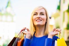 Verkauf, Einkaufen, Tourismus und Konzept der glücklichen Menschen - Schönheit mit Einkaufstaschen im ctiy lizenzfreies stockfoto