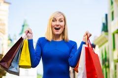 Verkauf, Einkaufen, Tourismus und Konzept der glücklichen Menschen - Schönheit mit Einkaufstaschen im ctiy lizenzfreie stockfotografie