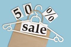 50% Verkauf Kraftpapiertasche und -aufhänger auf blauem Hintergrund Stockfotografie