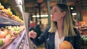 Verkauf, Lebensmittel, Einkaufen, Verbraucherschutzbewegung und Leutekonzept Blondine, die herein Früchte von den bunten Regalen  stock video footage
