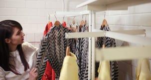 Verkauf, Mode, Verbraucherschutzbewegung und Leutekonzept - glückliche junge Frau, die Kleidung im Mall oder im Bekleidungsgeschä stock footage