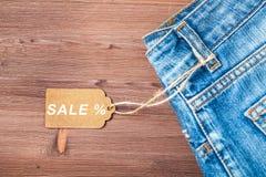 Verkauf, Rabatt, schwarzes Freitag-Konzept mit Tag, Blue Jeans auf einem hölzernen Hintergrund Draufsicht Copyspace Lizenzfreie Stockbilder