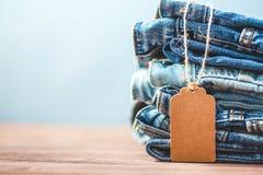 Verkauf, Rabatt, schwarzes Freitag-Konzept mit Tag, Blue Jeans auf einem hellen Hintergrund Copyspace Lizenzfreie Stockfotos
