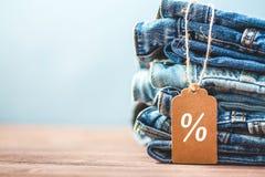 Verkauf, Rabatt, schwarzes Freitag-Konzept mit Tag, Blue Jeans auf einem hellen Hintergrund Copyspace Stockfotos