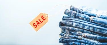 Verkauf, Rabatt, schwarzes Freitag-Konzept mit Tag, Blue Jeans auf einem hellen Hintergrund Roter Verkauf Copyspace-Fahne singt Stockfoto