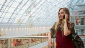 Verkauf, Verbraucherschutzbewegung: Junge Frau mit den Smartphones und Einkaufstaschen, die nahe Einkaufszentrum stehen und sprec stock video footage