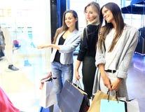 Verkauf, Verbraucherschutzbewegung und Leutekonzept - glückliche überraschte junge Frauen mit Einkaufstaschen Finger auf Shopfens stockbilder