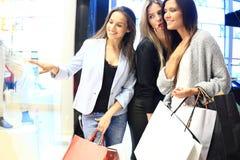 Verkauf, Verbraucherschutzbewegung und Leutekonzept - glückliche überraschte junge Frauen mit Einkaufstaschen Finger auf Shopfens lizenzfreie stockfotografie