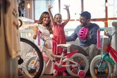 Verkauf, Verbraucherschutzbewegung und Leutekonzept - glückliche Familie mit Kind und kaufendem neuem Fahrrad stockbild