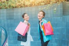Verkauf, Verbraucherschutzbewegung und Leutekonzept - glückliche junge Frauen, die in Einkaufstaschen Shop in der Stadt betrachte stockbild