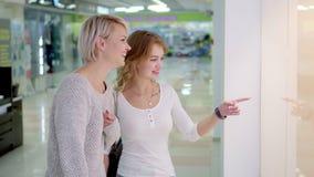 Verkauf, Verbraucherschutzbewegung und Leutekonzept - glückliche junge Frauen, die Finger zeigen, um zu kaufen Fenster in der Sta stock footage
