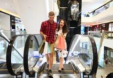 Verkauf, Verbraucherschutzbewegung und Leutekonzept - glückliches junges Paar mit den Einkaufstaschen, die in Mall gehen stockbilder