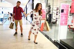 Verkauf, Verbraucherschutzbewegung und Leutekonzept - glückliches junges Paar mit den Einkaufstaschen, die in Mall gehen stockfotografie
