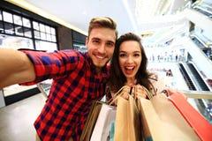Verkauf, Verbraucherschutzbewegung und Leutekonzept - glückliches junges Paar mit den Einkaufstaschen, die in Mall gehen stockfotos