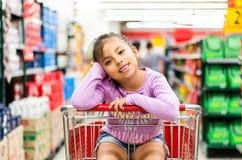Verkauf, Verbraucherschutzbewegung und Leutekonzept - glückliches kleines Mädchen im Einkaufswagen stockbild