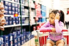 Verkauf, Verbraucherschutzbewegung und Leutekonzept - glückliches kleines Mädchen nachdenklich im Einkaufswagen lizenzfreies stockbild