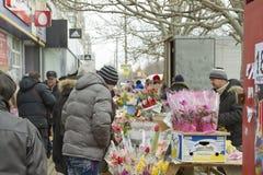 Verkauf von Blumen und von Blumensträußen an der Straße Leutekaufblumen in einem Geschenk am 8. März Stockbild