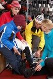 Verkaufs-behilfliche helfende Familie, zum der Skistiefel ein zu versuchen Stockbild