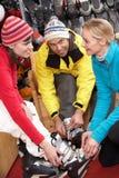 Verkaufs-behilfliche helfende Paare, zum der Skistiefel ein zu versuchen Lizenzfreie Stockfotos