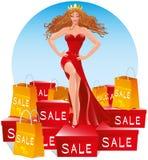 Verkaufs-Königin Schönheit in einem langen roten Abendkleid steht auf vielen Kästen mit Käufen Stockfotografie