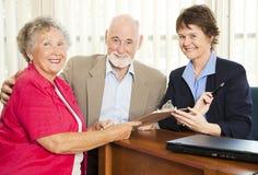 Verkaufs-Person und ältere Paare Lizenzfreie Stockfotografie