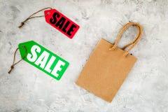 Verkaufsaufkleber nahe Papiereinkaufstasche auf grauem Draufsichtmodell des Hintergrundes Lizenzfreie Stockfotografie