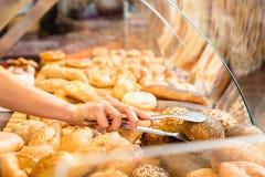 Verkaufsfrau im Bäckershop, der Brötchen in Papiertüte einsetzt stockfoto