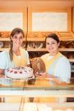 Verkaufsfrauen in der Bäckerei mit Kuchen und Brot Lizenzfreie Stockbilder
