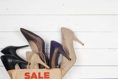 Verkaufsfrauenschuhe in den hohen Absätzen und in den Einkaufstaschen Stockfotografie