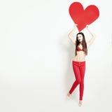 Verkaufskonzept - Hand mit Vergrößerungsglas Mode-Frau, die großes rotes Fahnen-Herz hält Lizenzfreie Stockbilder