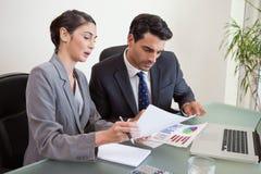 Verkaufspersonen, die mit einem Notizbuch arbeiten Lizenzfreie Stockfotos