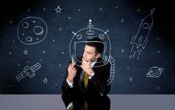 Verkaufspersonenzeichnungssturzhelm und -Weltraumrakete Stockfotos