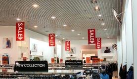 Verkaufsposter an der Mode kleidet shopfront Stockbilder