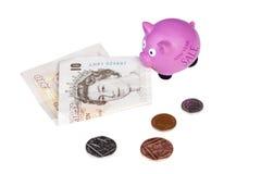 Verkaufsschwein des neuen Jahres, das eine zehn-Pfund-Anmerkung isst Stockfoto