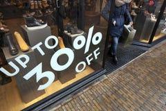 Verkaufszeichen- und -rabattzahlen auf Shopfenster des Schuhgeschäfts Stockfoto