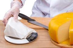 Verkauft durch das Wiegen eines Stückes Käses Lizenzfreie Stockbilder