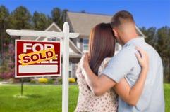 Verkauft für Verkaufs-Zeichen mit den Militärpaaren, die Haus betrachten stockfotografie