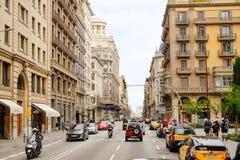 Verkeer in een straat van Barcelona met mooie gebouwen langs de kant van de weg stock afbeelding