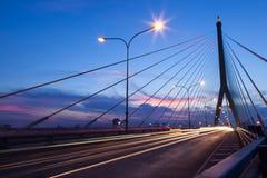 Verkeer op brug bij avond. Stock Afbeelding